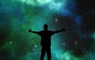 person with arms open to expansive quantum universe